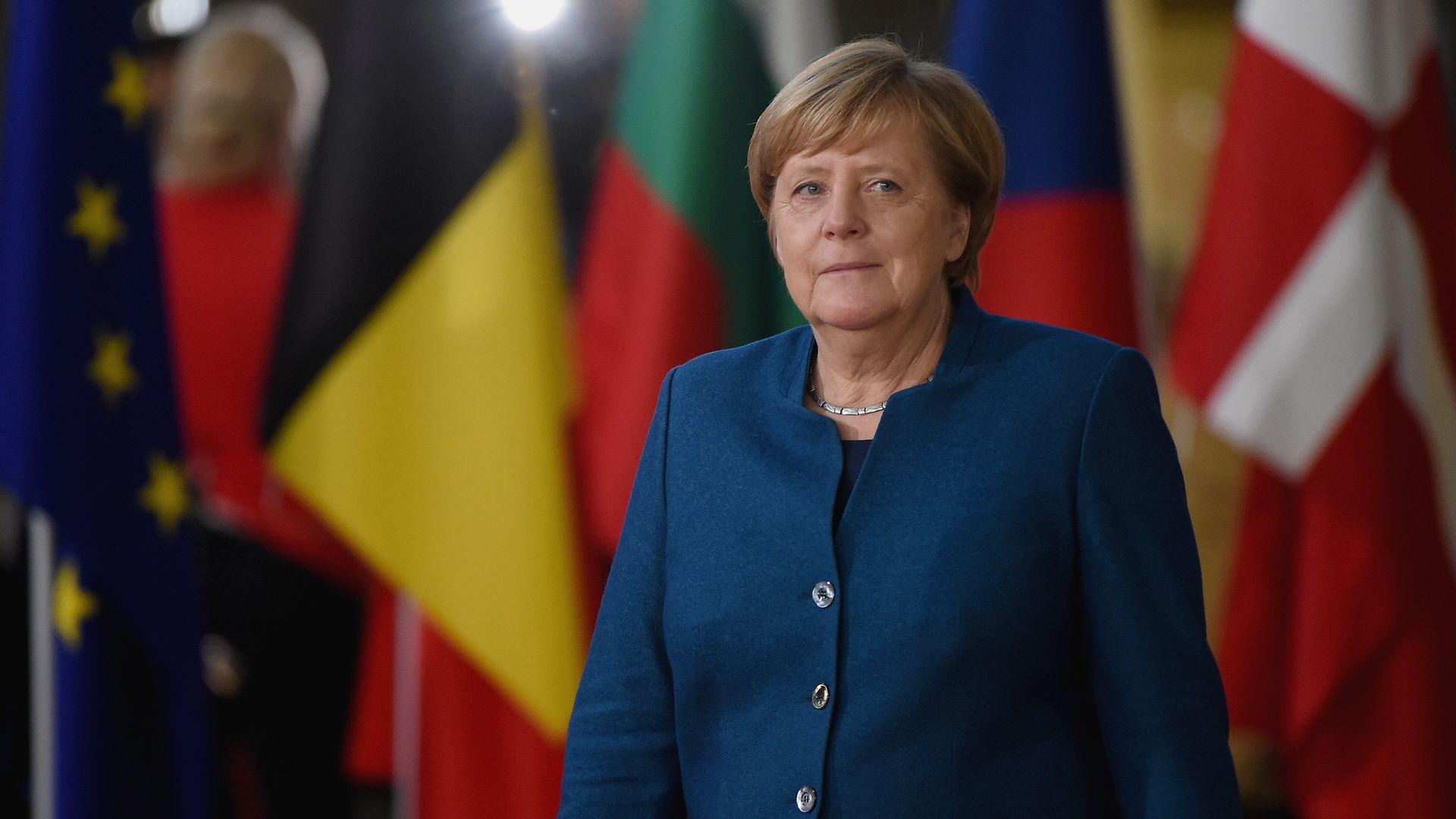 Angela Merkel standing in front of european flags in a blue pantsuit.