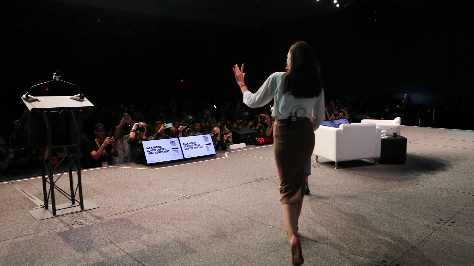 AOC walks onstage at a conference