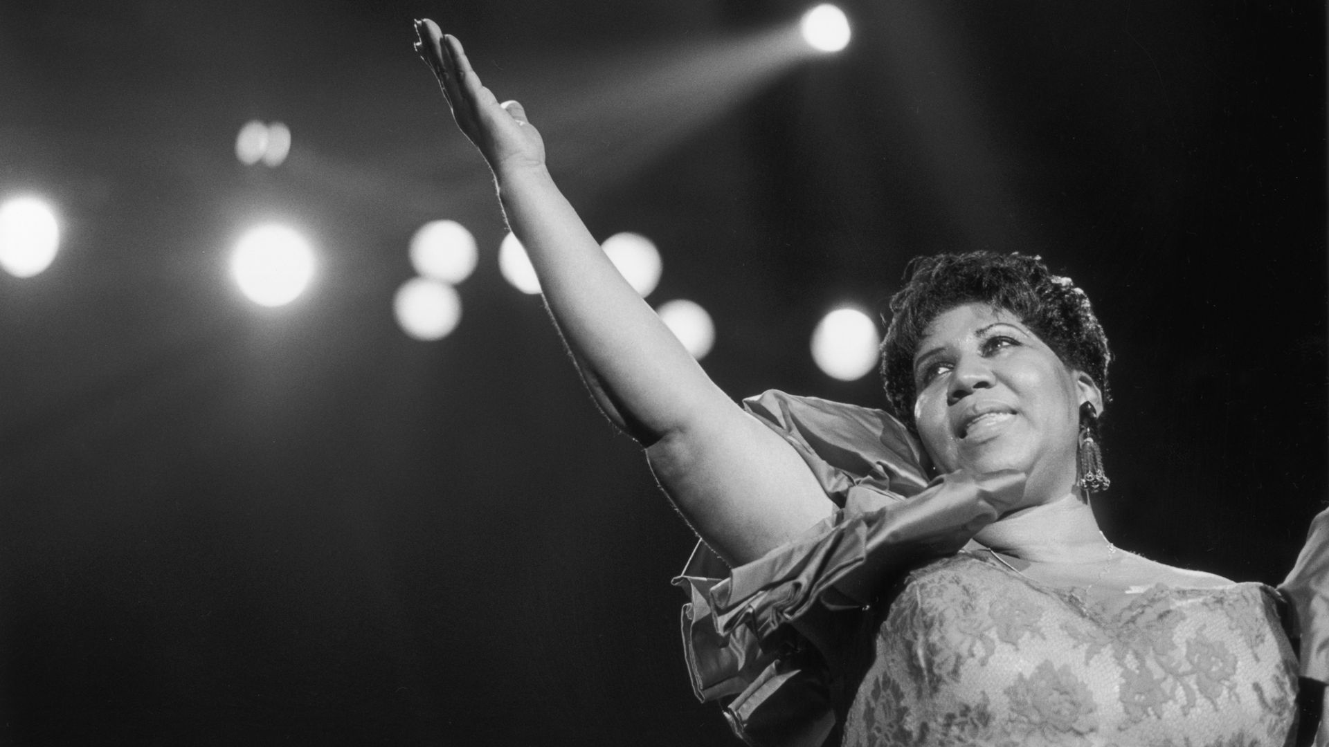 A black-and-white photo of Aretha Franklin singing.