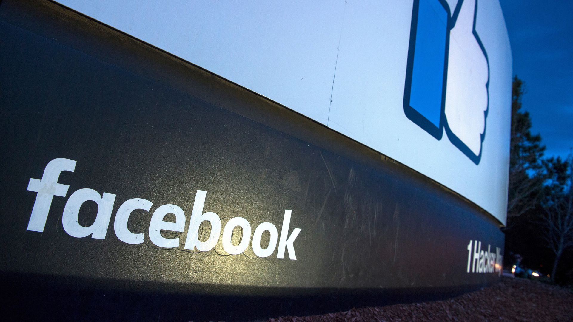 "An angled-up photo of the ""thumbs up"" sign outside Facebook HQ at night"