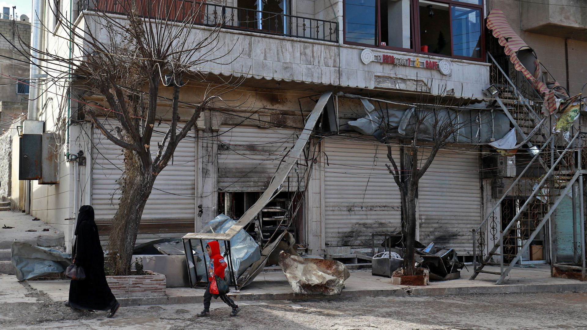 A Syrian woman and child walk past the shuttered doors of a restaurant which was the site of a suicide attack in northern Syria which killed four US servicemen.