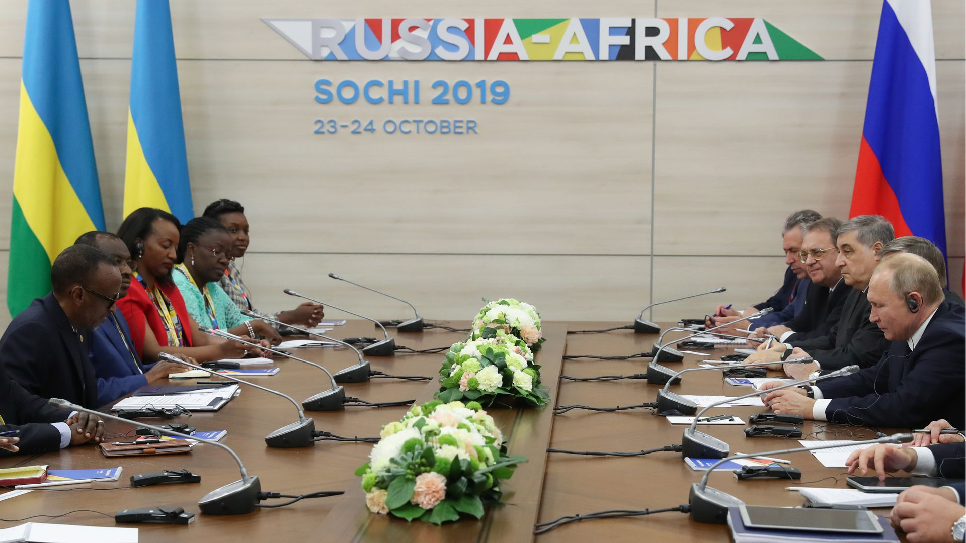 Putin, Kagame and fellow Russian and Rwandan officials seated across a conference table