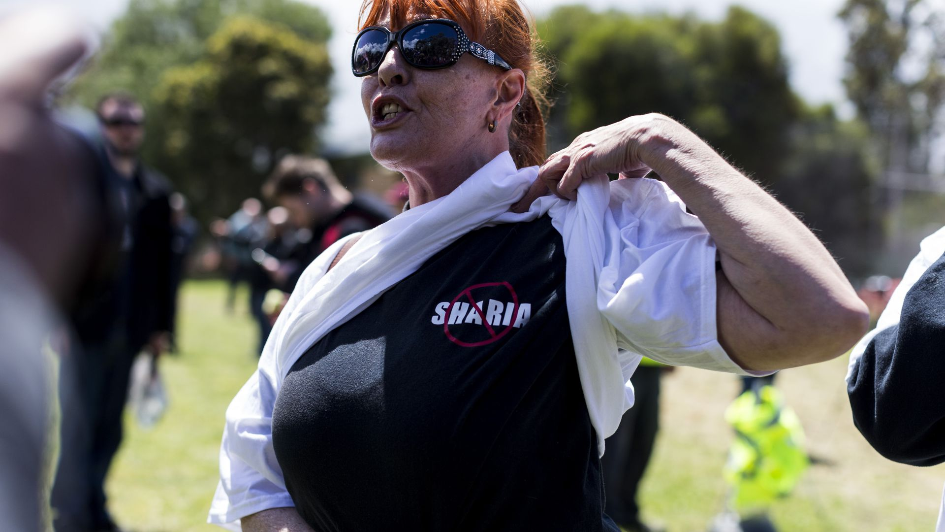 "A woman reveals a shirt under her sweatshirt that has a red ""no"" symbol over the word Sharia."