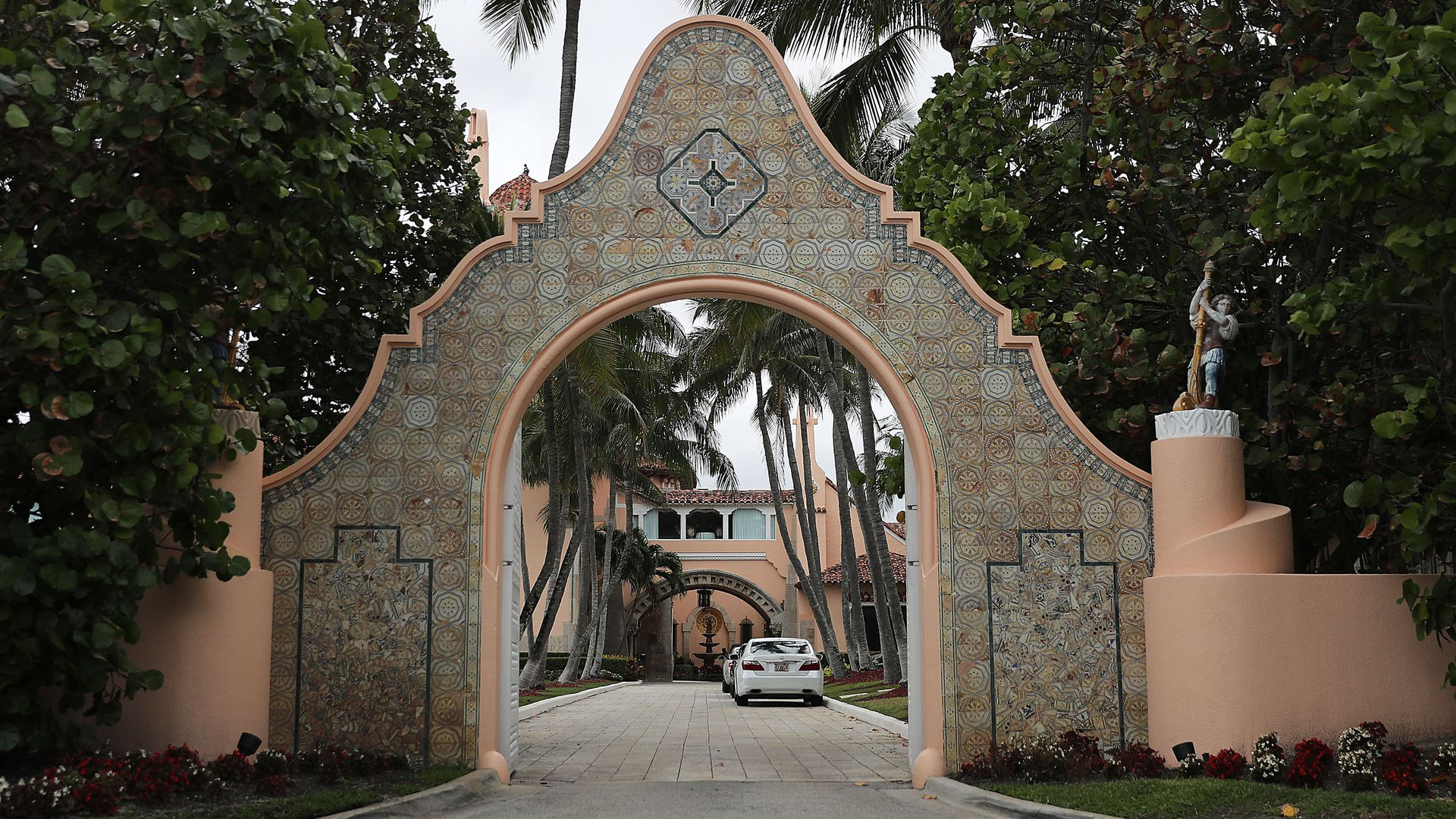 This image shows a stone entranceway to Mar-a-lago, framed by palm trees.