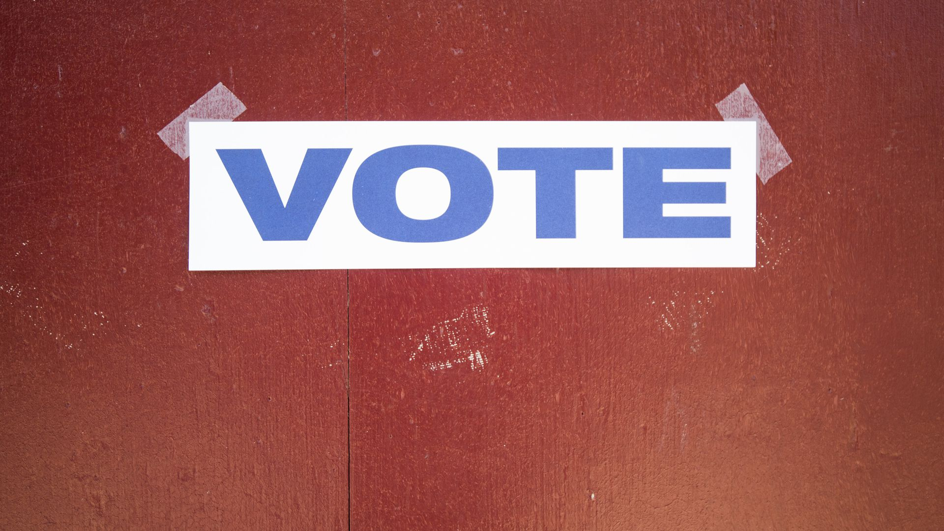 Sign that says vote in all caps in blue on white paper taped to red wood door.