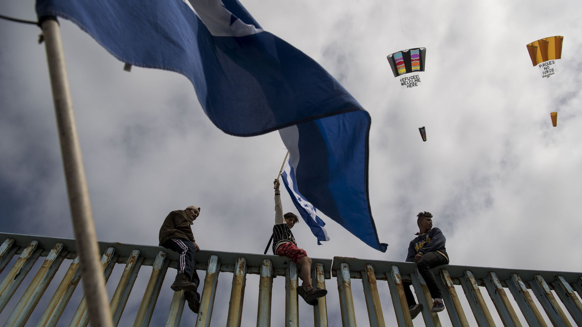 Three immigrants from Central America sit on top of the border wall with a flag flying in the foreground.