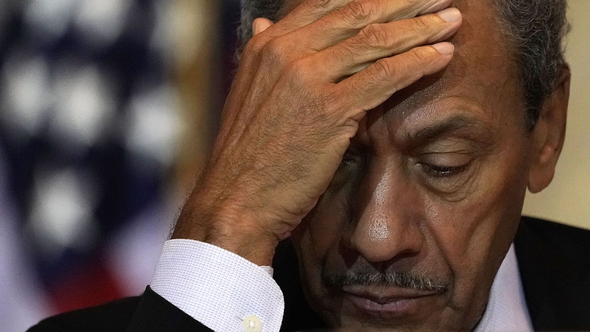 In this image, former congressman Mel Watt looks down and away from the camera, partially covering his face with one hand.