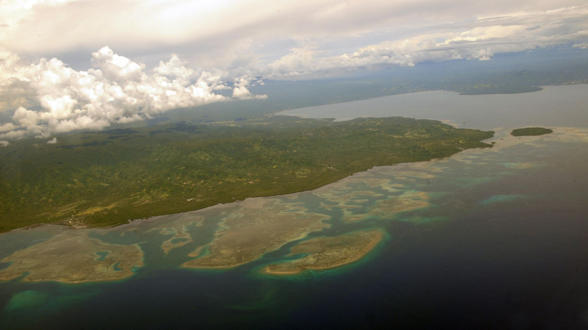 The coast of northern Sulawesi is seen from a plane approaching the capital city of Manado