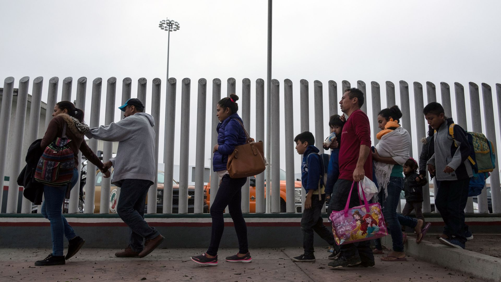 A line of adults and children walk toward a port of entry with a fence next to them.