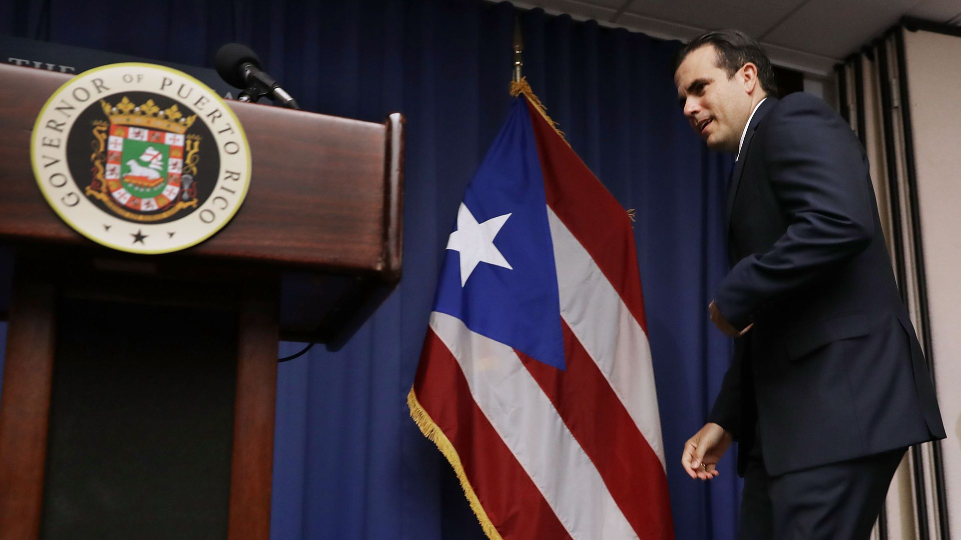 Puerto Rico Gov. Ricardo Rosselló walks up to a podium with the Puerto Rican flag behind him.