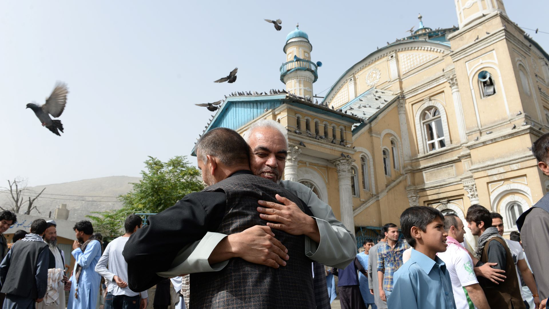 Men hug in front of a mosque in Kabul