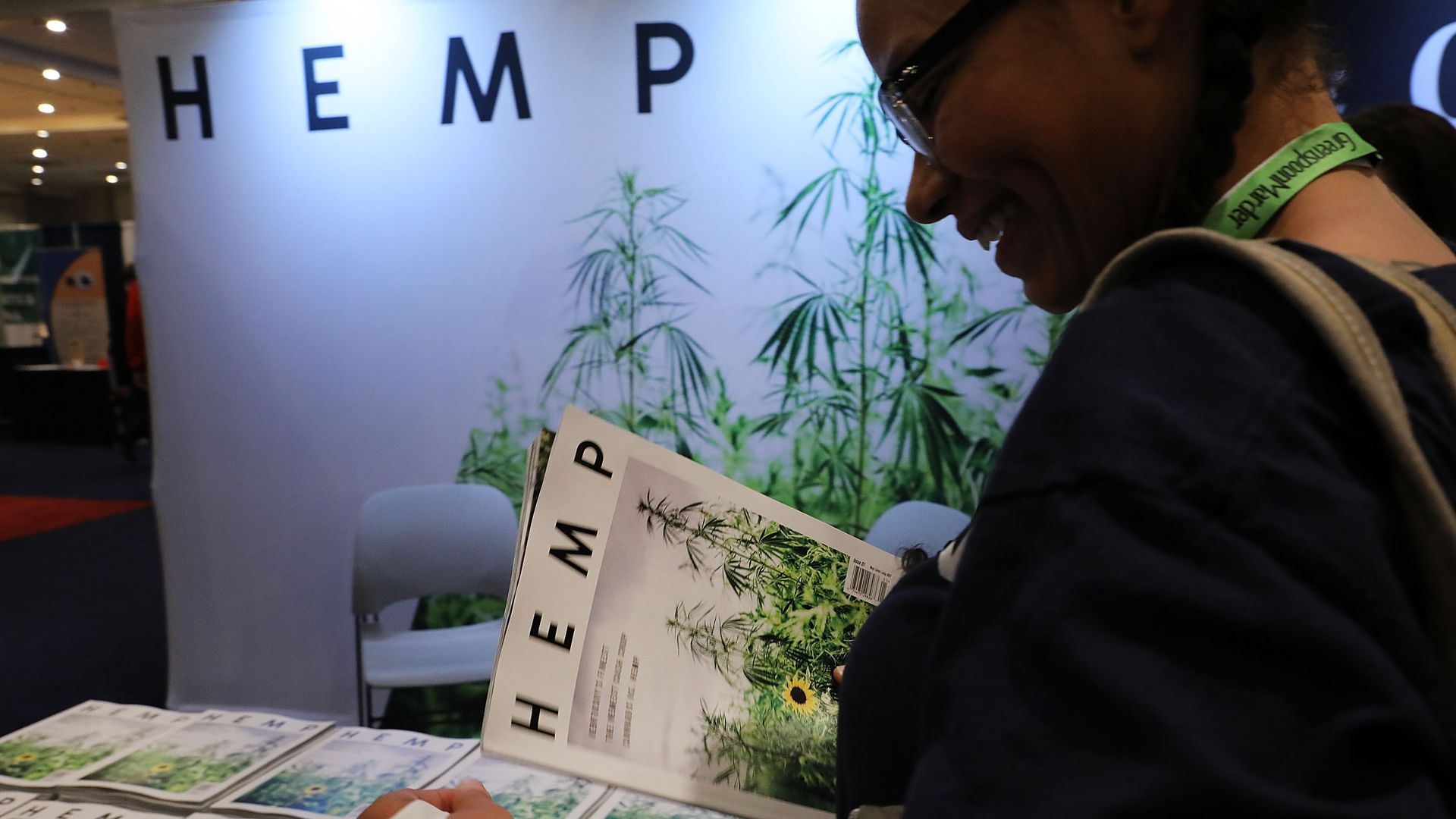 "Signs and someone holding a magazine that says ""hemp"" on it"