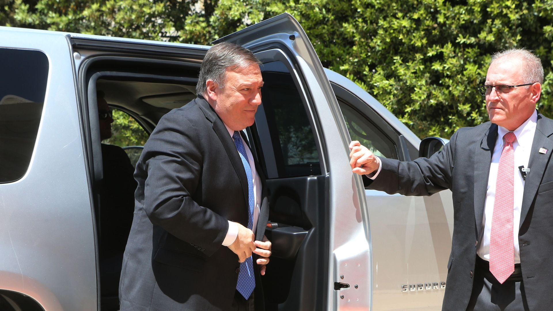 Mike Pompeo pulls his suitcoat together to button it as he steps out of a silver car.