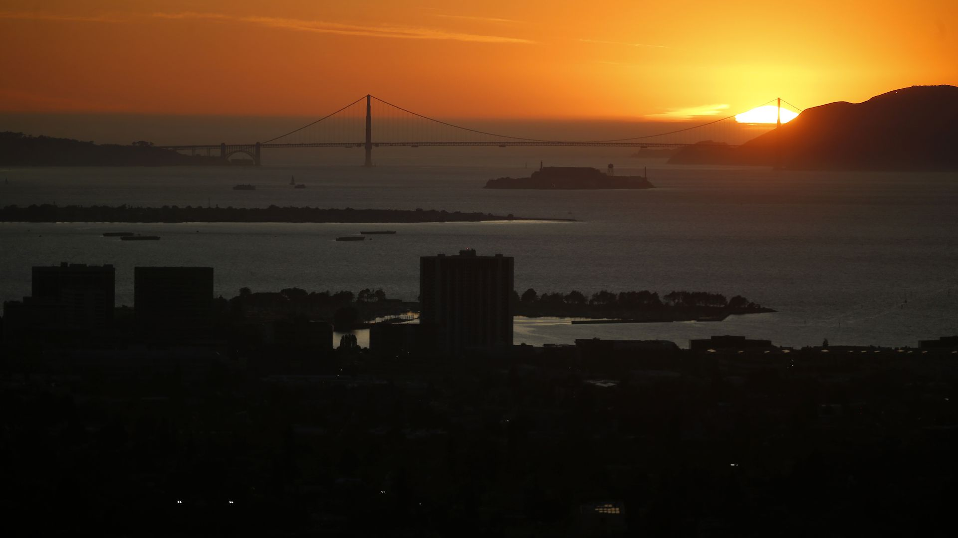 This image shows a dark San Francisco skyline during a sunset, with the darkened Golden Gate bridge in the distance