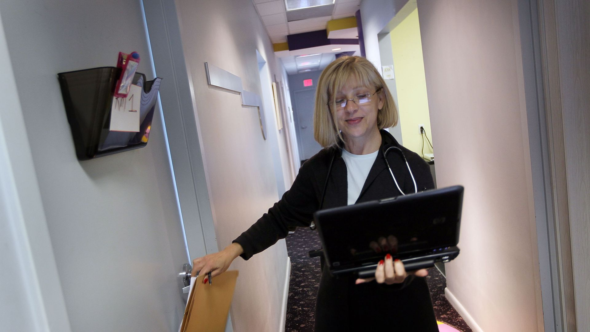 A doctor holds a laptop before entering a patient room.