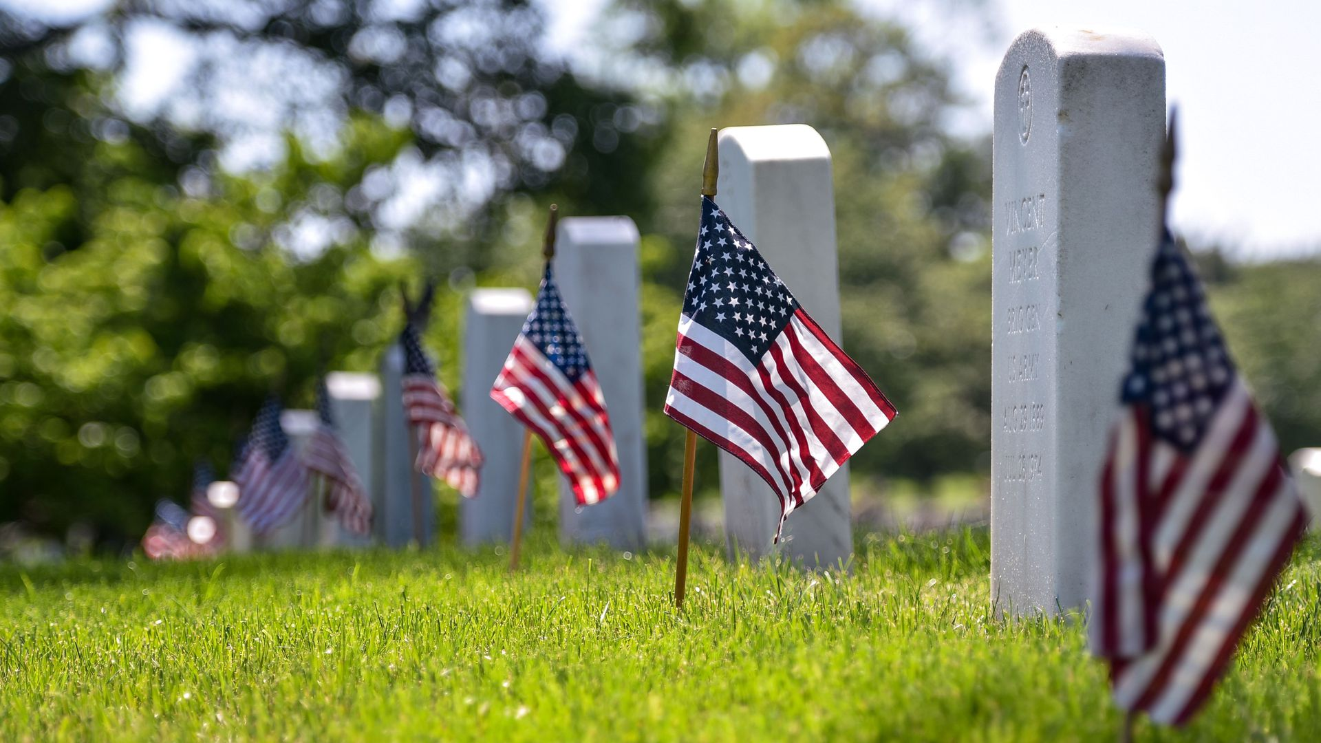 Flags in front of headstones at Arlington National Cemetery.