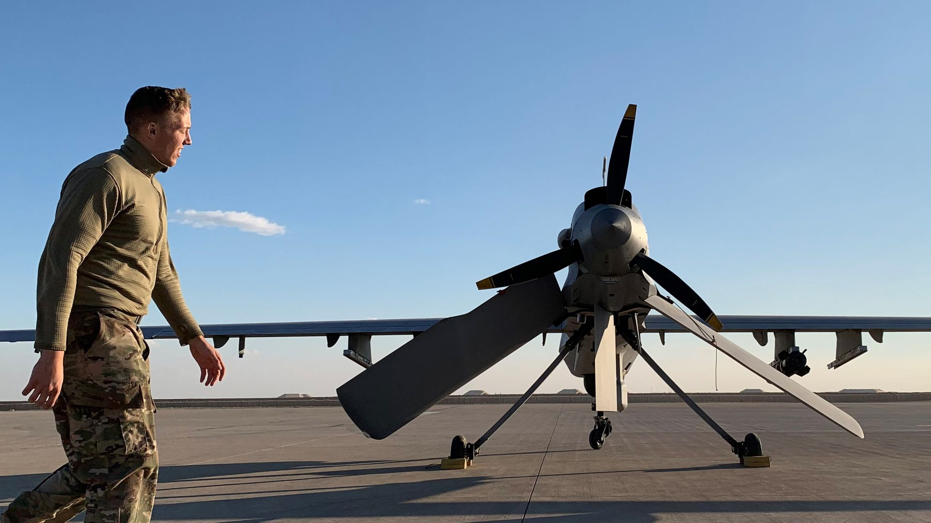 In this image, a US soldier in Iraq walks past a military plane