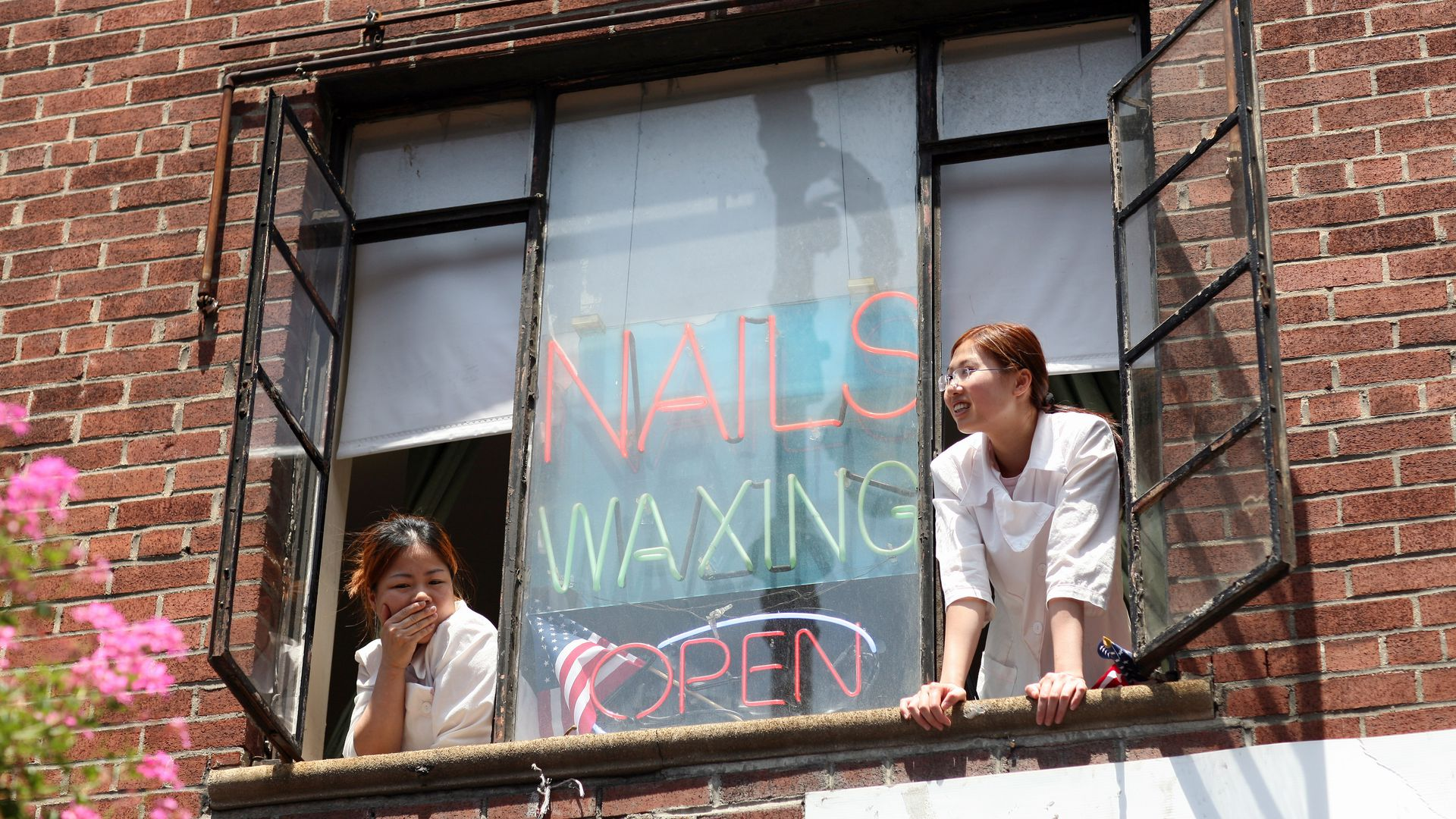 Two women look out the window of a salon
