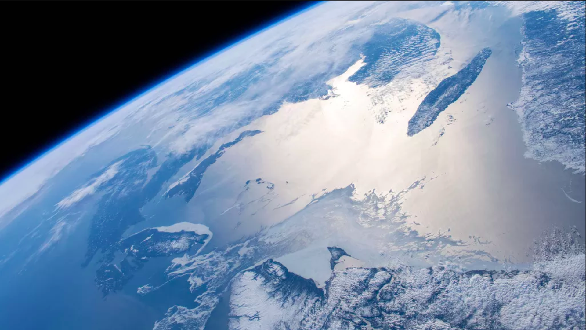 This image is a view of a quarter of the earth from space. It's mostly blue, with some glaciers.