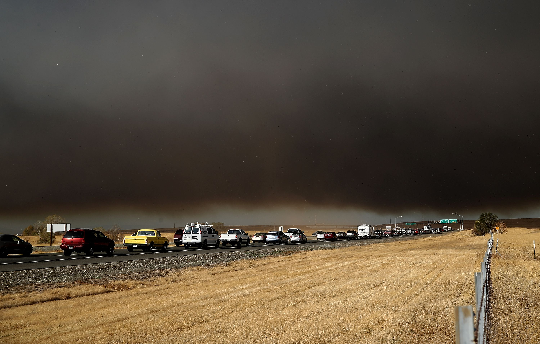 Traffic sits under heavy black smoke.