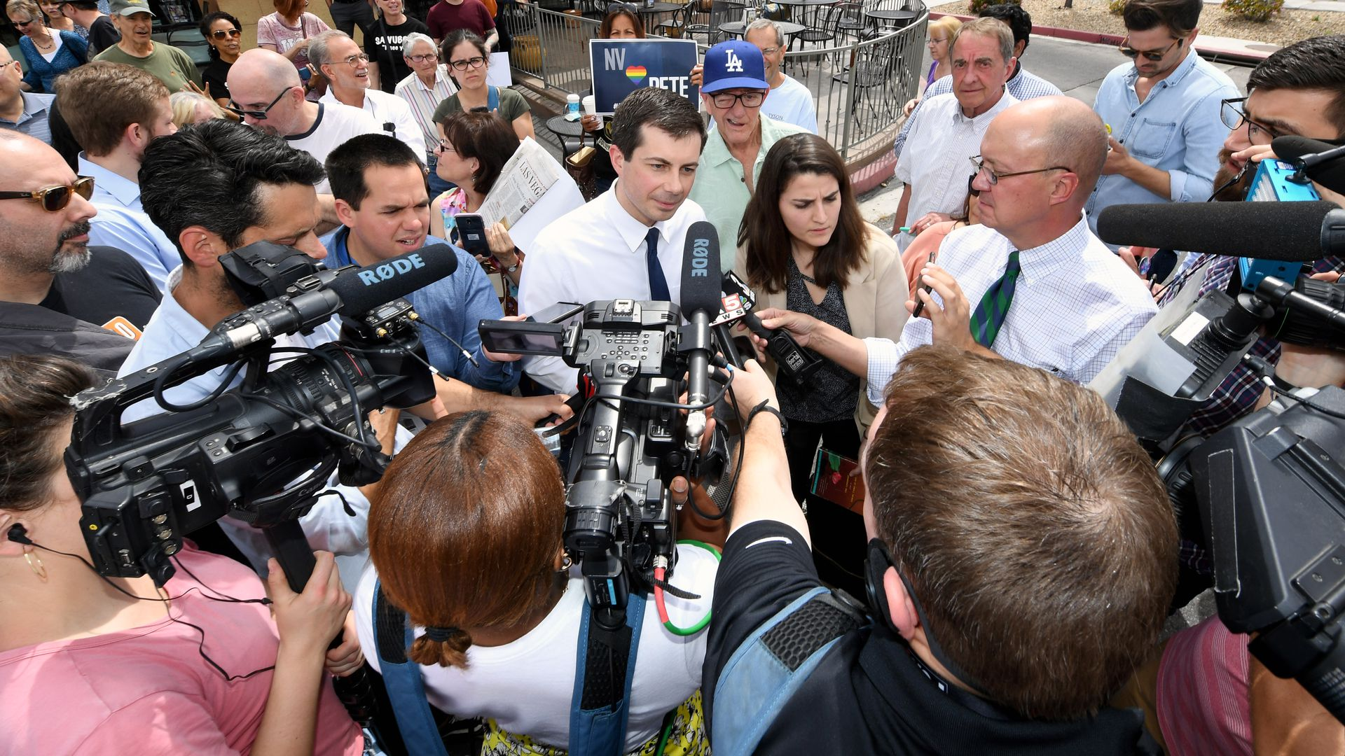 In this image, Pete Buttigieg stands in the center of a crowded ring of reporters who hold microphones towards him.