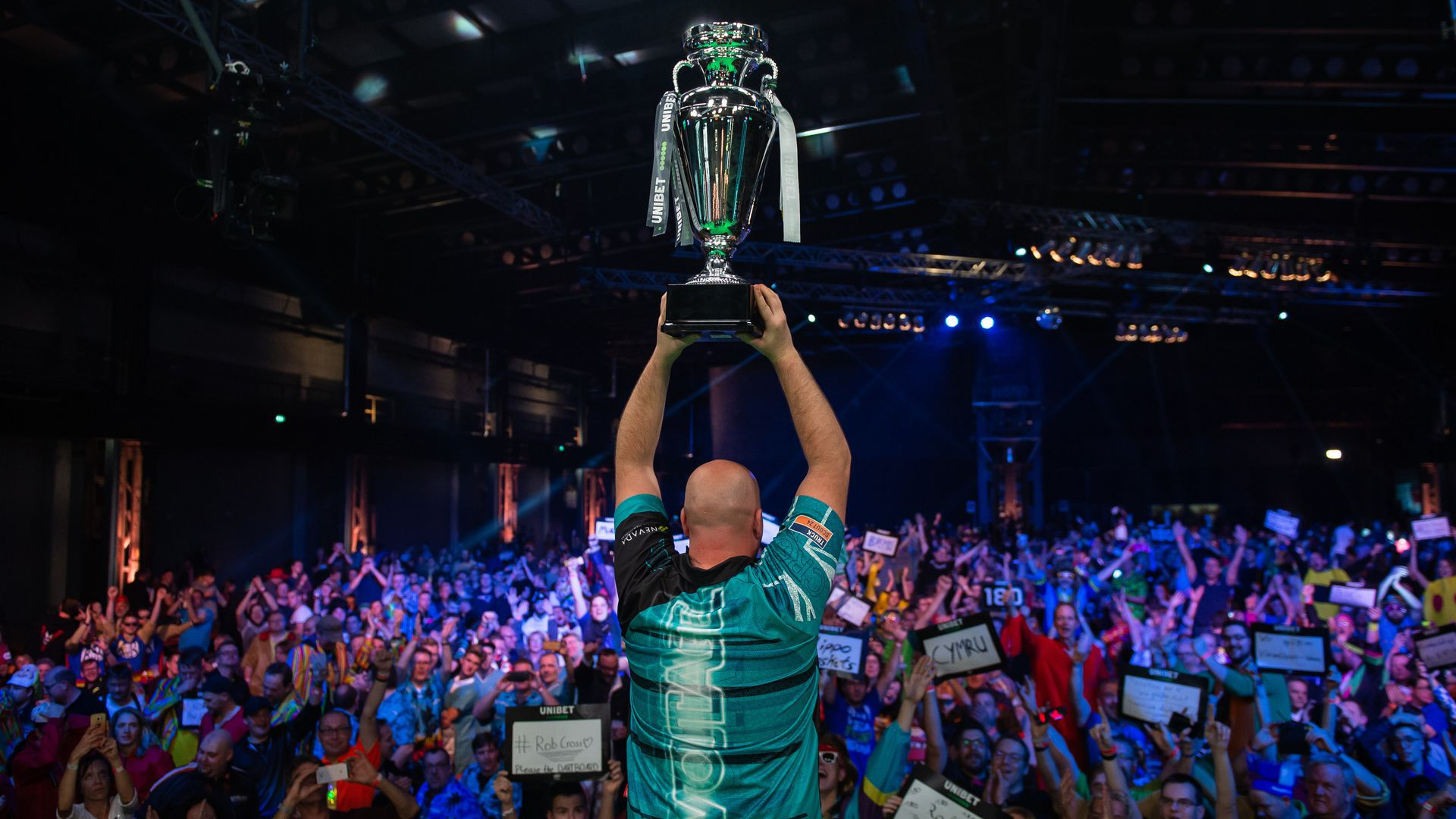 Rob Cross holding a trophy.