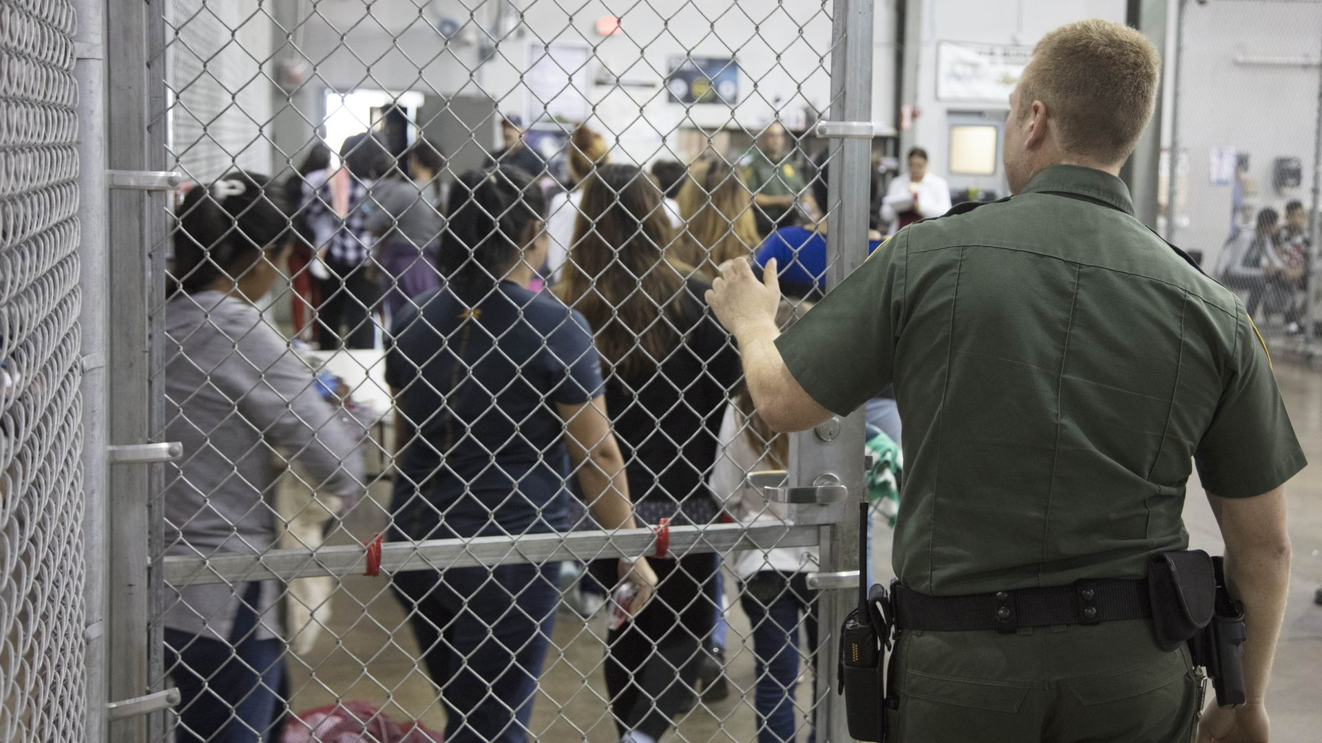 In this image, a CBP officer is seen from behind, closing a gated door.
