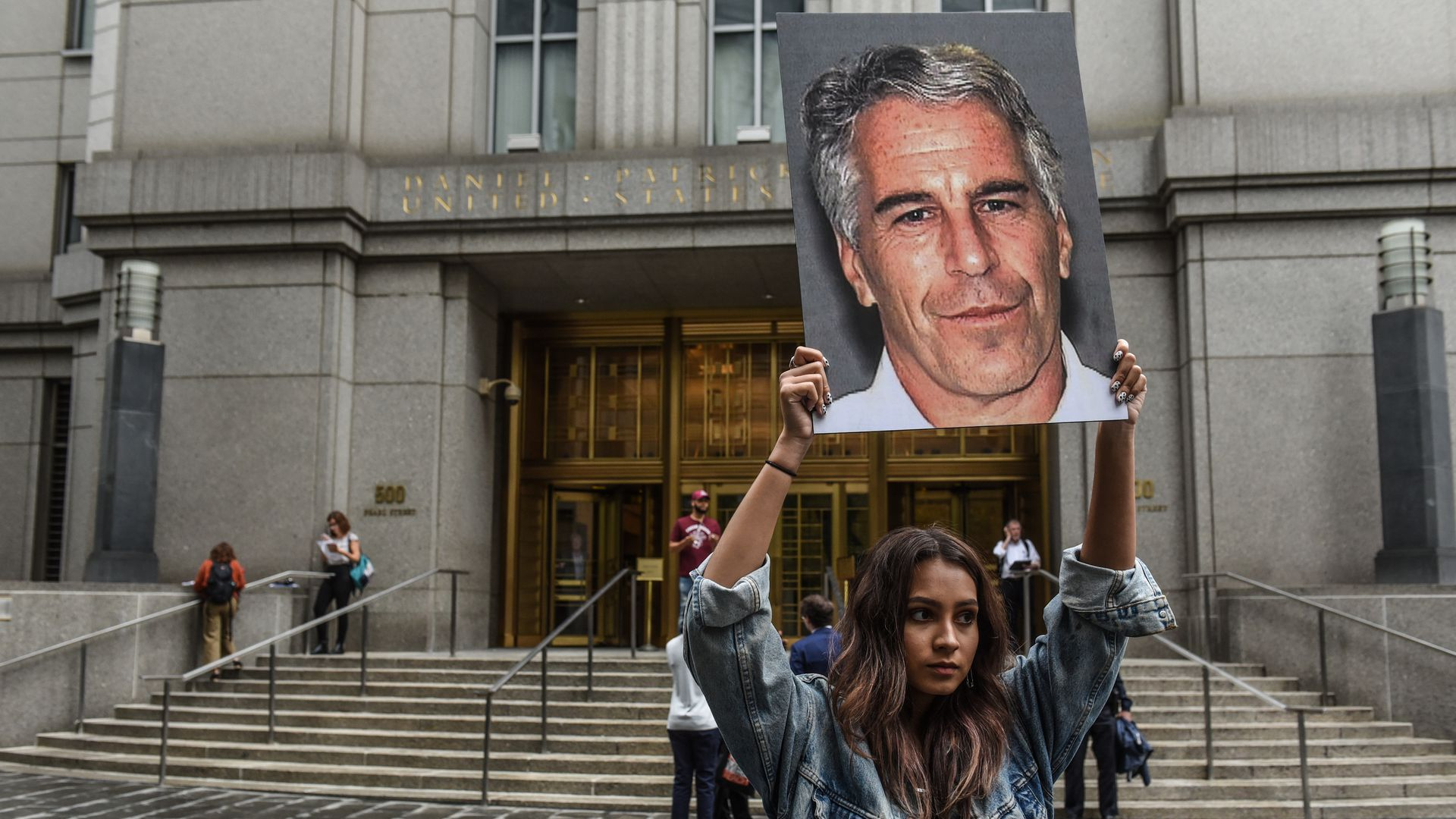 A girl holding up a poster of Epstein's face.