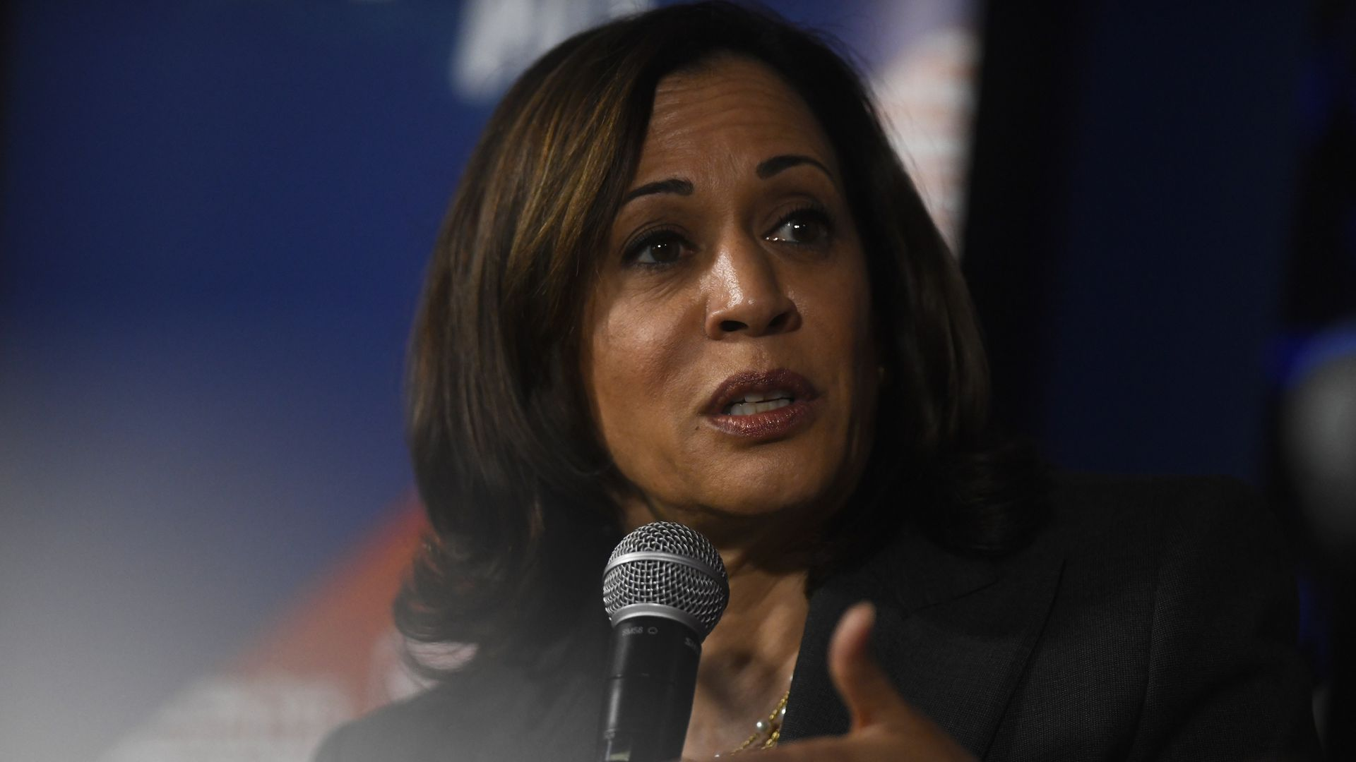 In this image, Kamala Harris speaks into a microphone while wearing a blazer.