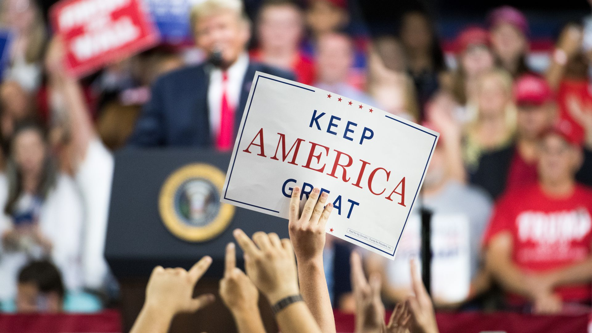"""Supporters at a Trump rally hold up a """"Keep America Great"""" sign"""