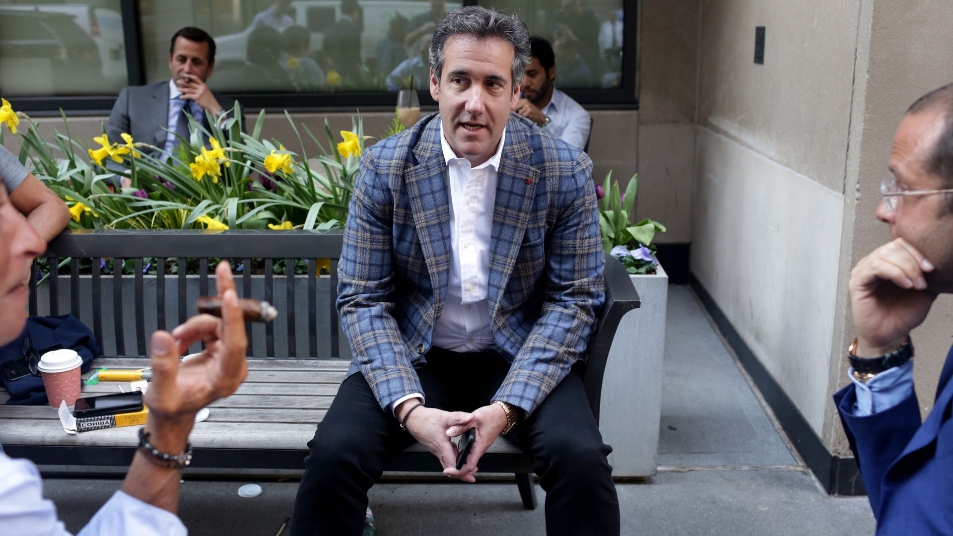 Michael Cohen sitting on a bench, talking