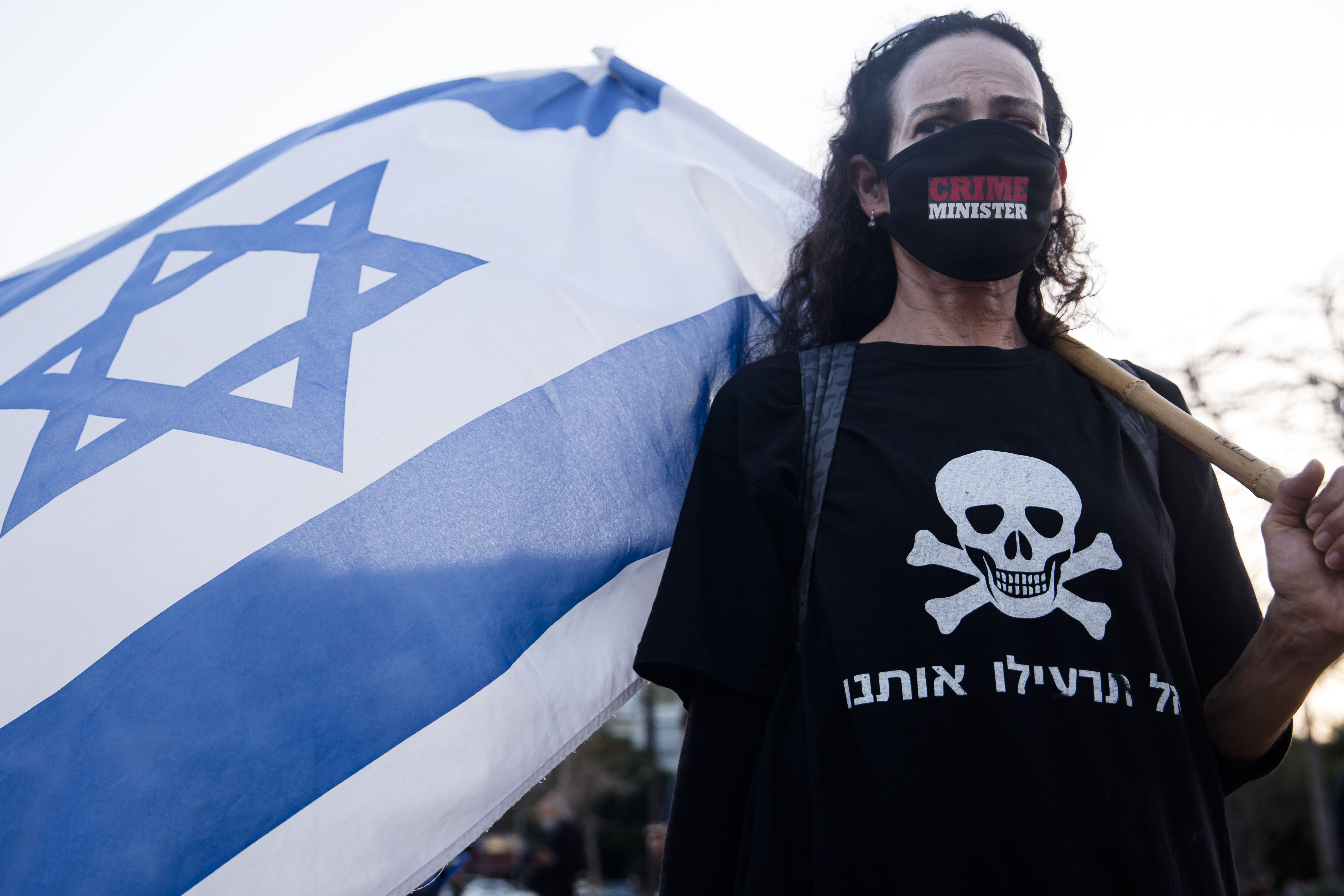 Woman wearing facemask and protesting Netanyahu