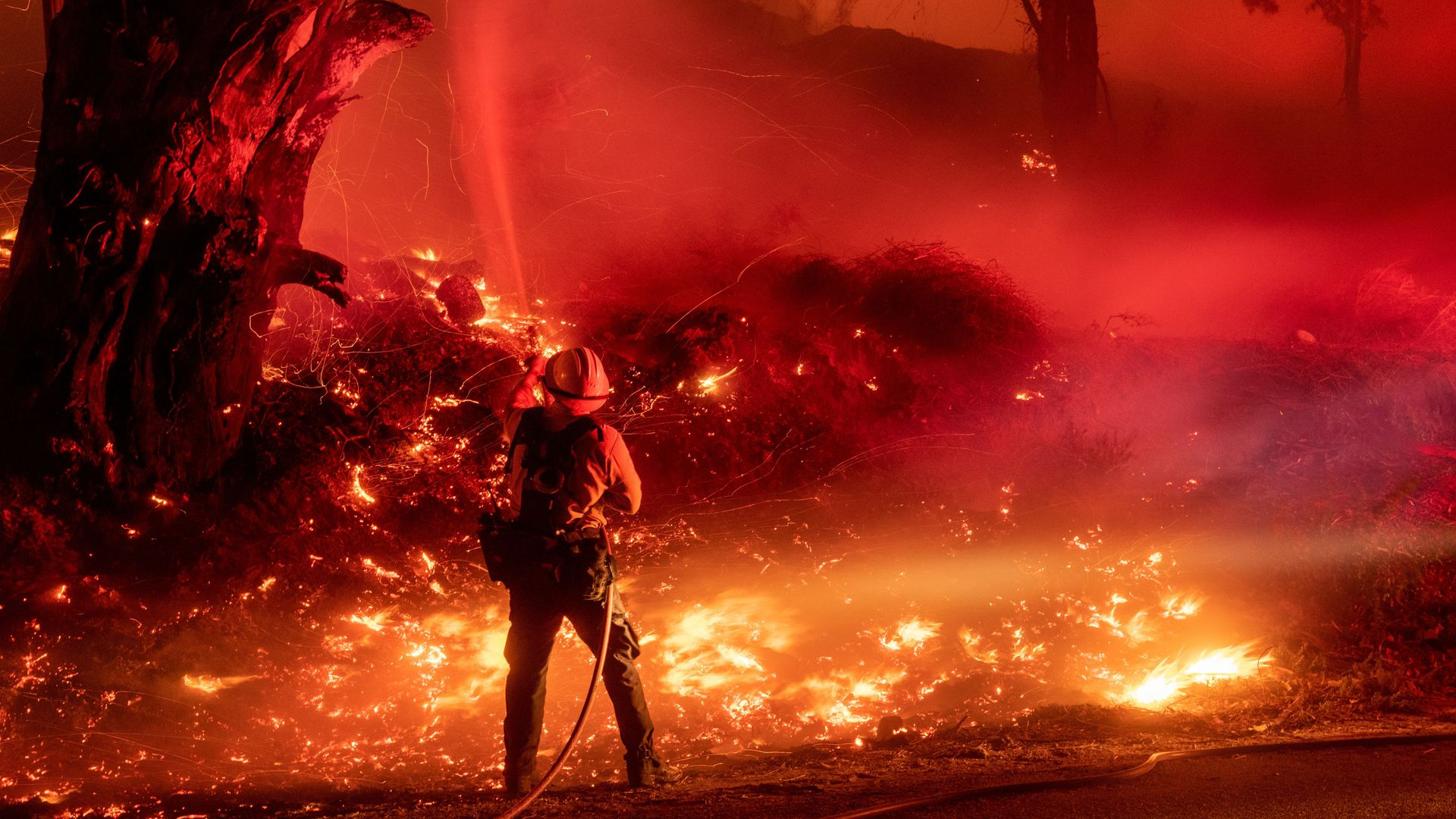 A firefighter douses flames from a backfire during the Maria fire in Santa Paula, California on November 1