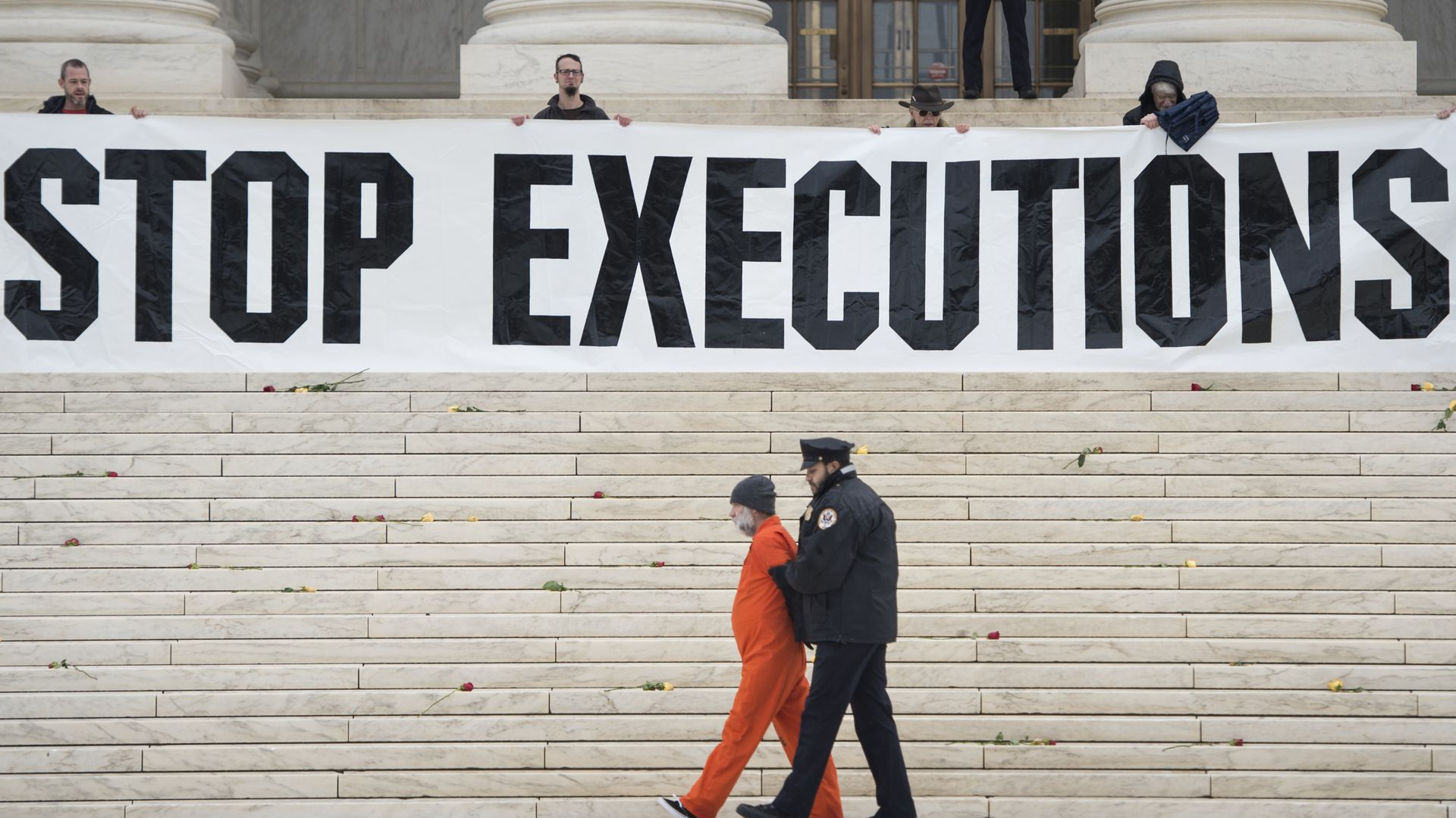 "man in orange jumpsuit being escorted by police officer sign that says ""stop executions"" is being held in the background"