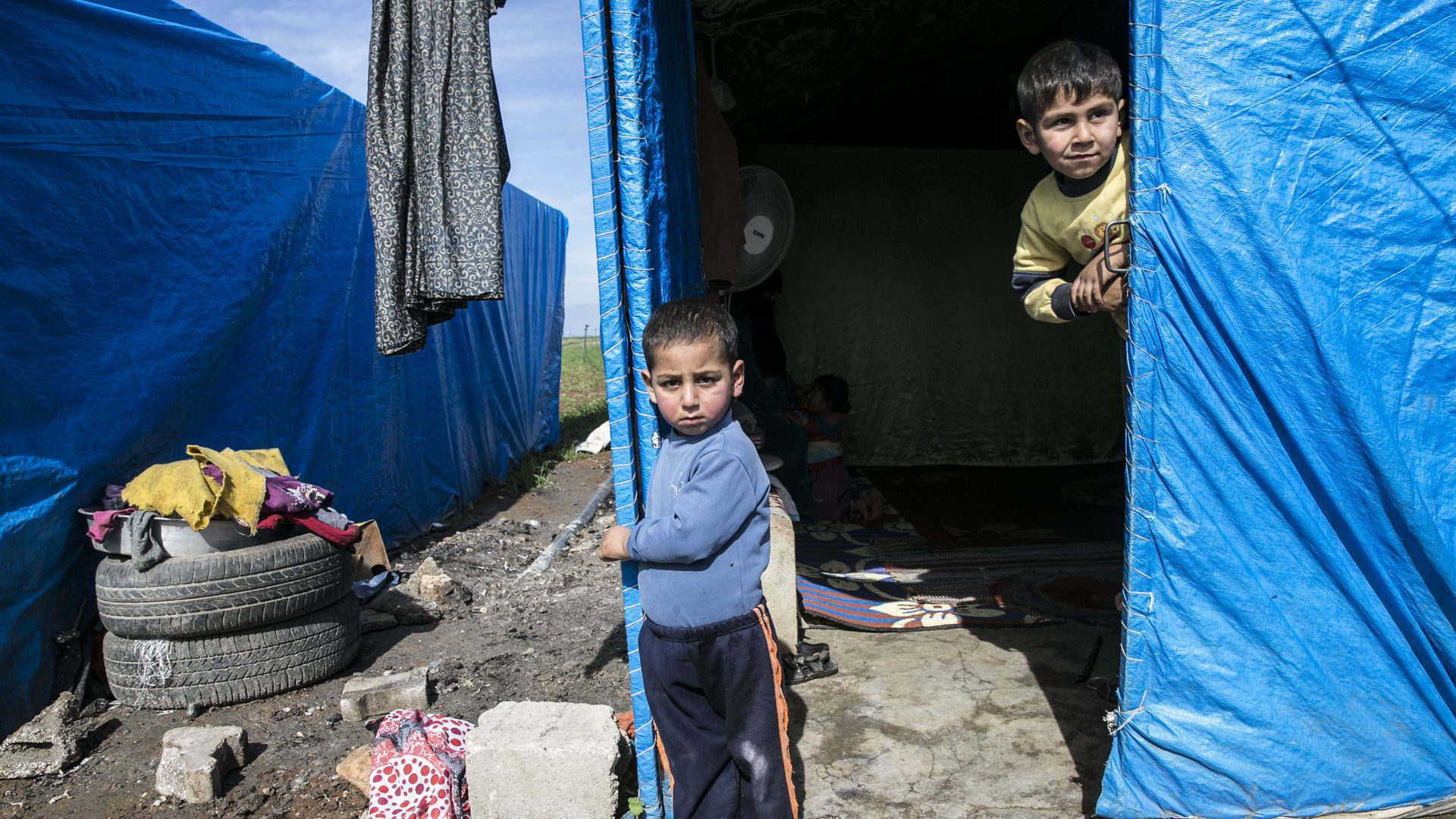 Syrian children next to a tent in a refugee camp