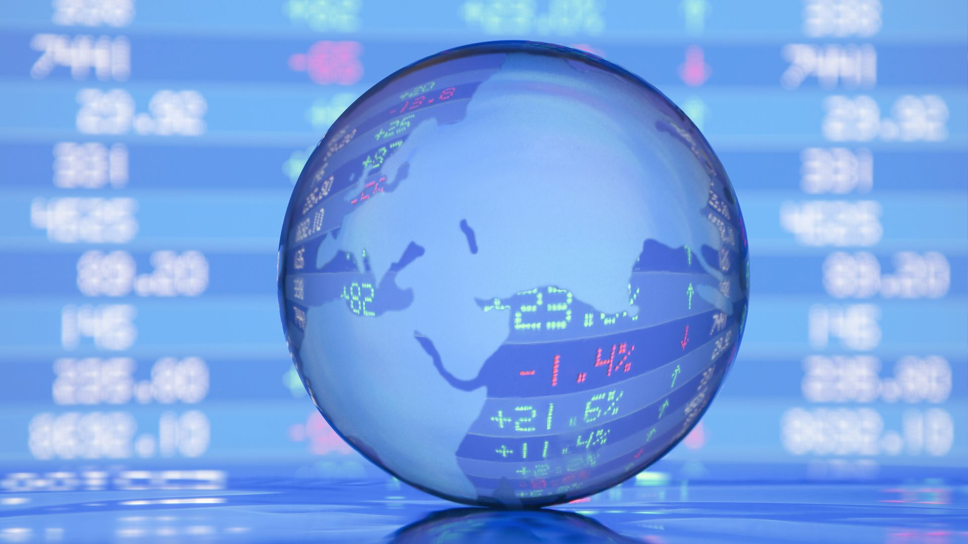 A globe in front of stock market listings