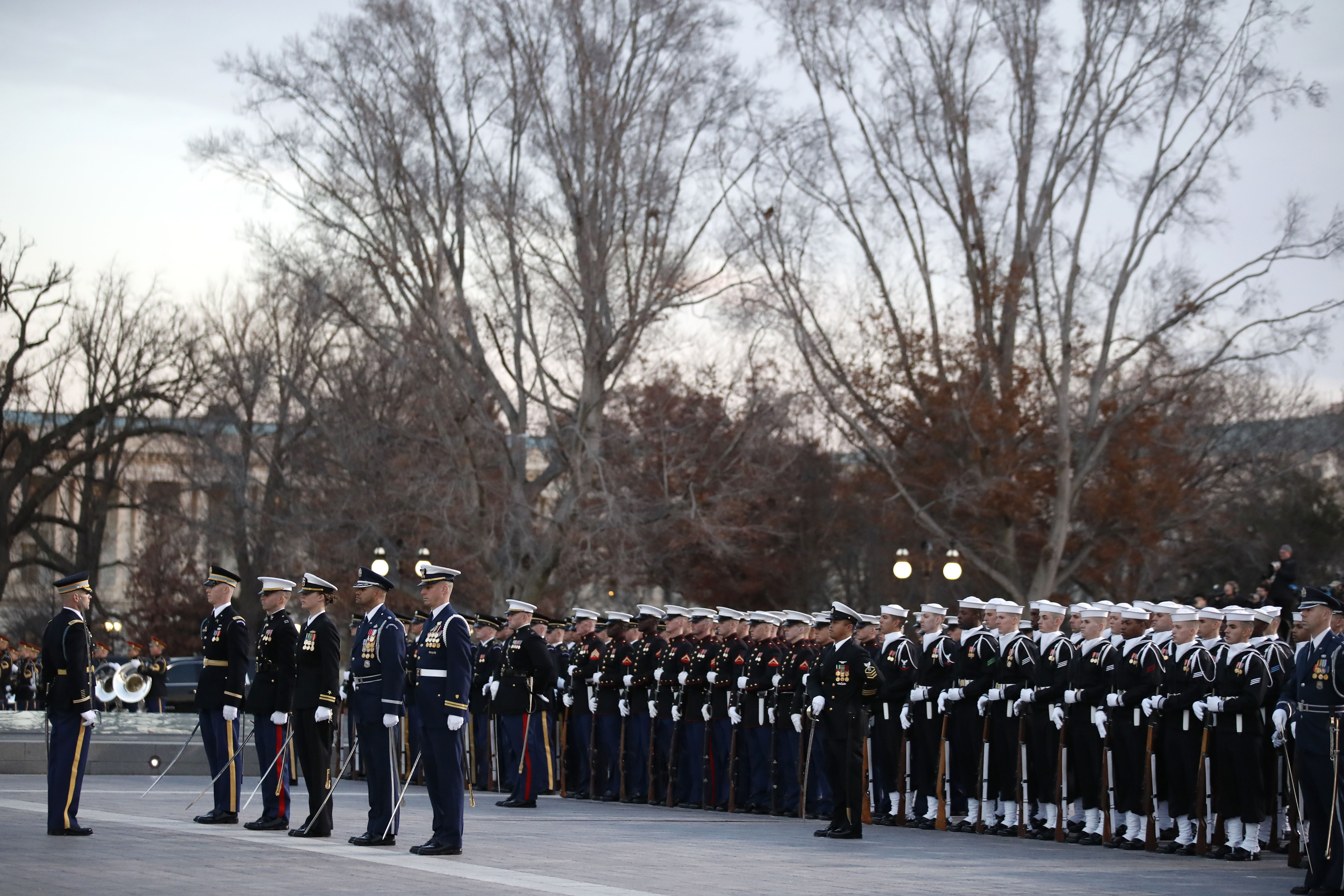 Member of the military salute as George H. W. Bush's casket arrives on Capitol Hill.