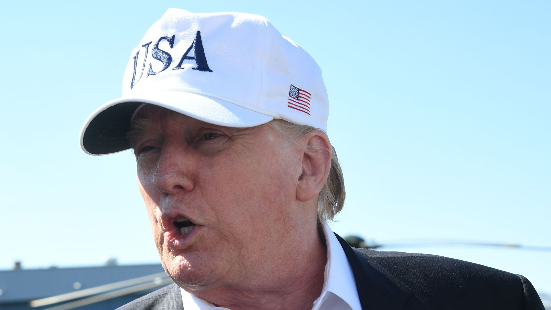 Donald Trump speaks with mouth open before a blue sky wearing a white USA hat.