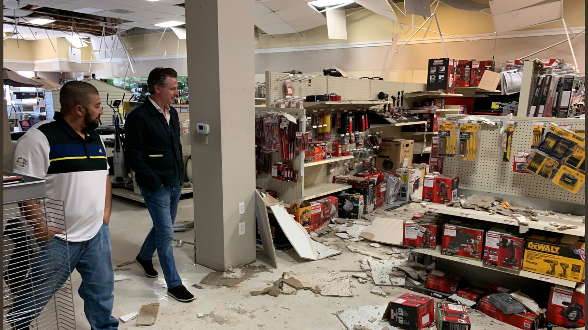 California Gov. Gavin Newsom assesses the quake damage in a store.