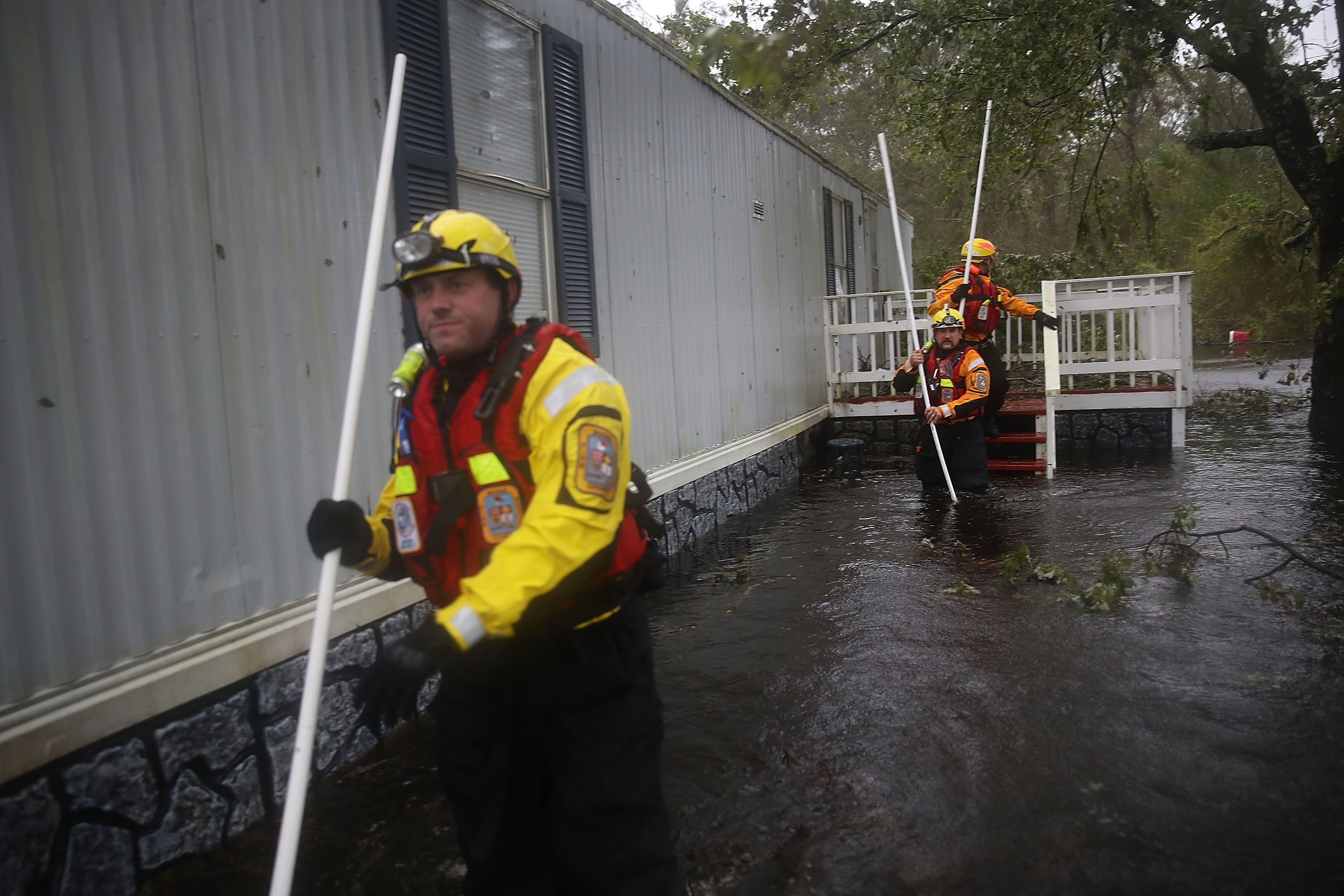 Fire rescue workers wading through water.