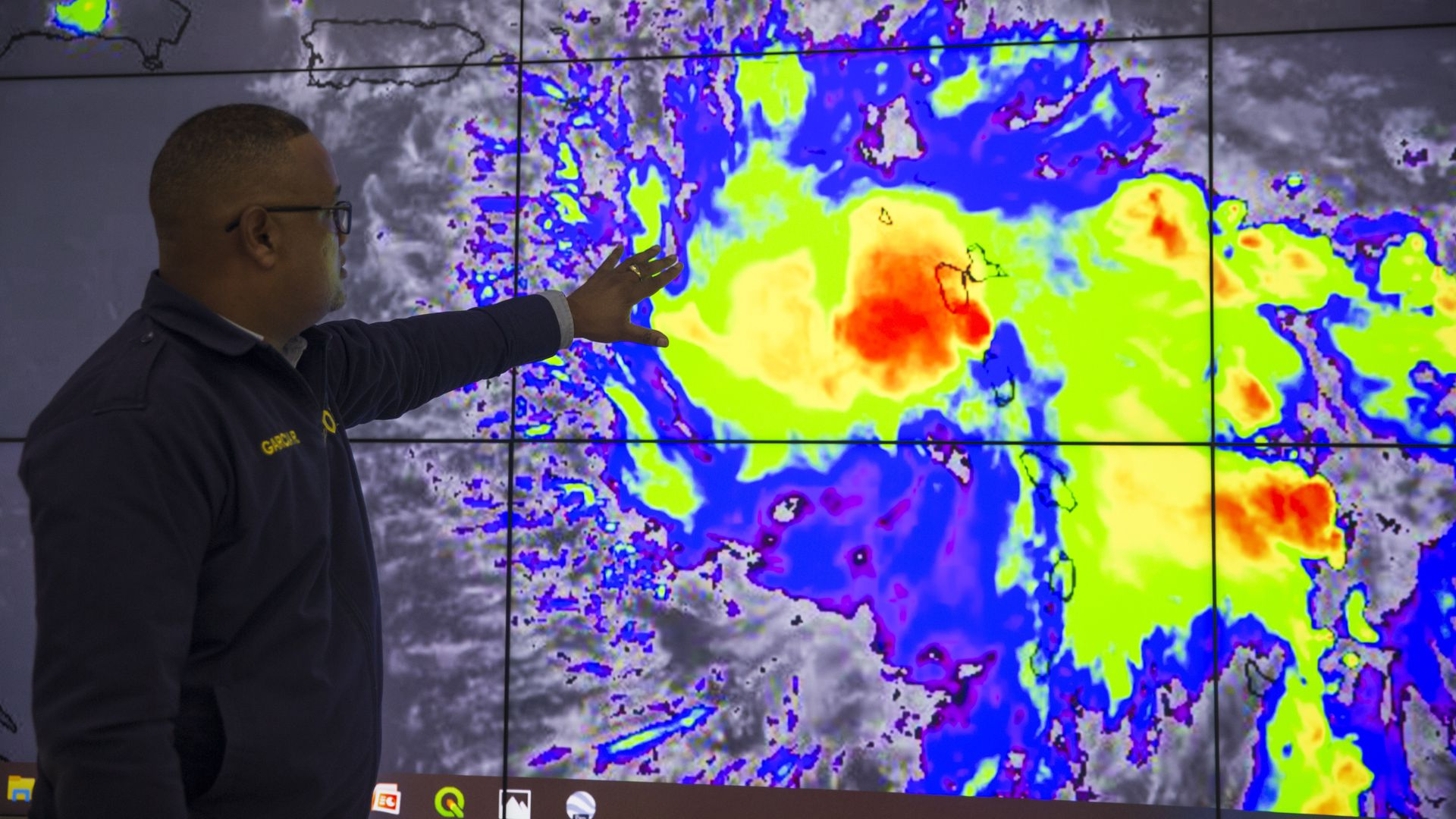 In this image, a man outstretches a hand towards a weather map that shows a tropical storm in different colors