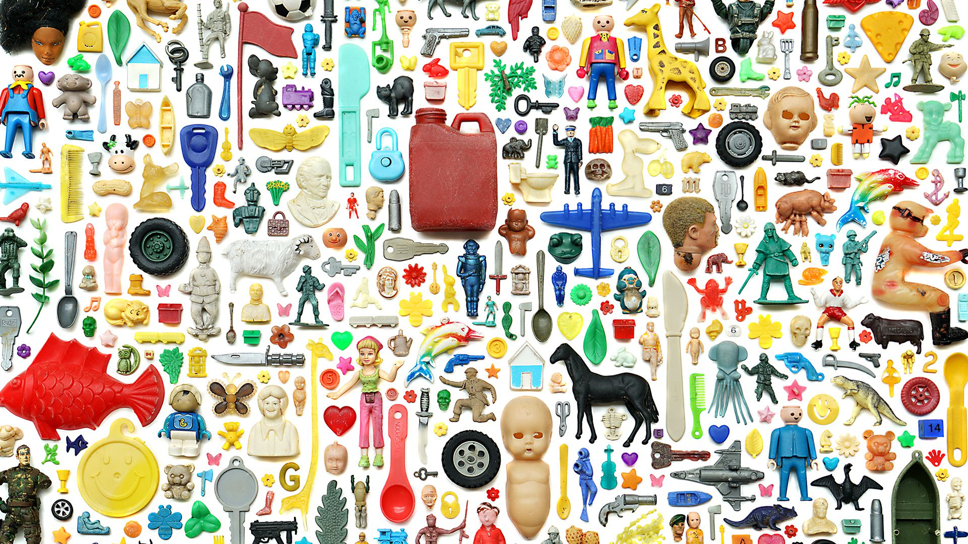 Image of many assorted, small plastic objects like doll heads, planes, eating utensils, arranged into a montage.