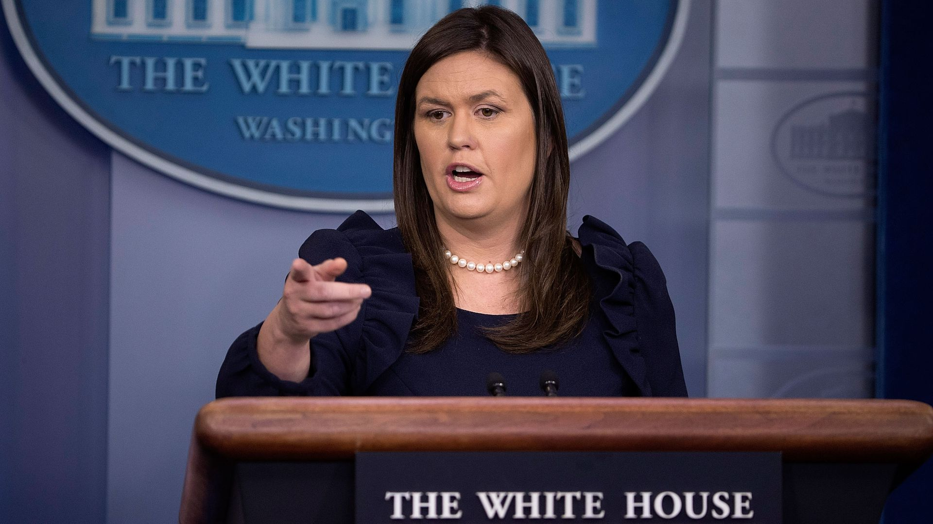 Sarah Sanders points to a reporter while speaking at the podium