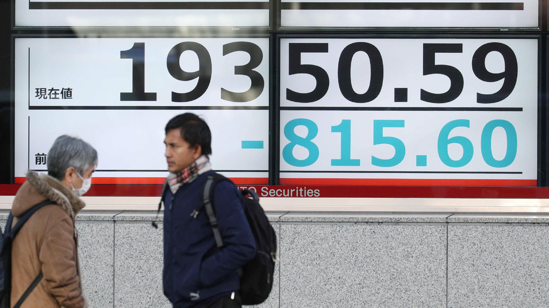 Pedestrians walk past a board showing the share price of the Tokyo Stock Exchange