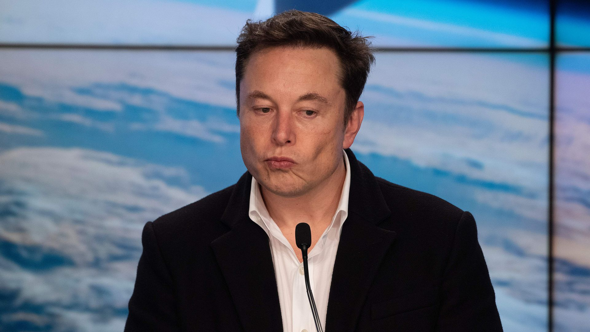 In this image, Elon Musk looks down while standing in front of a microphone. He's wearing a suit with no tie.