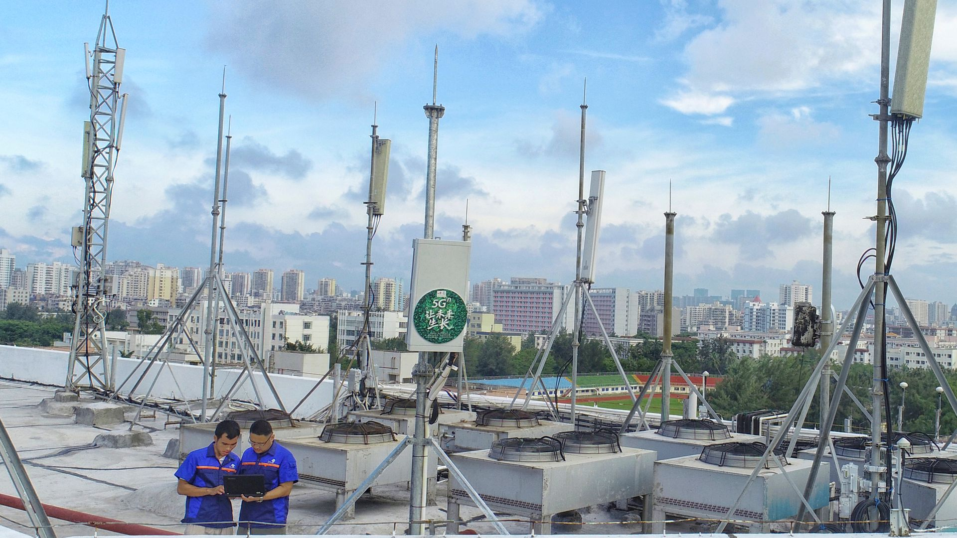 Photo of two men looking at a tablet near rooftop 5G antennas