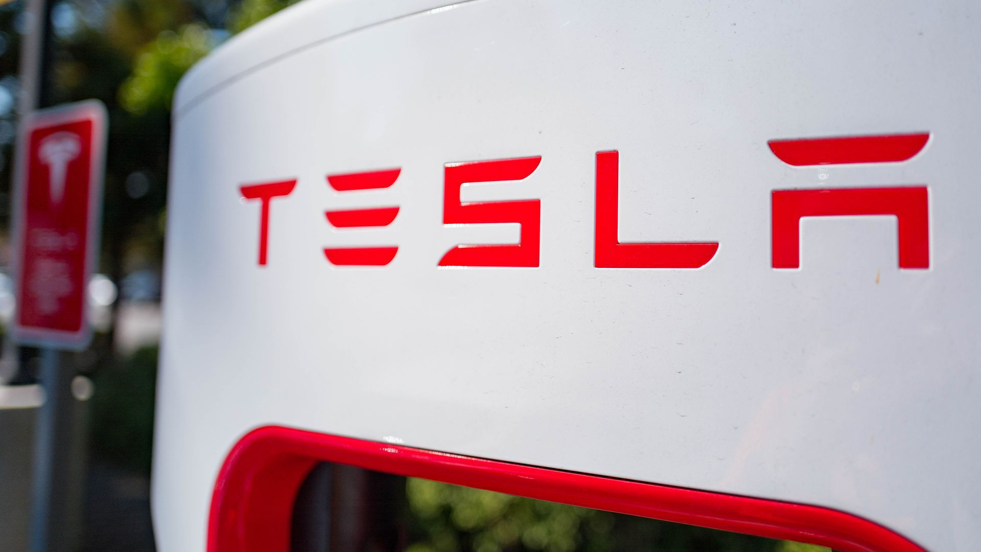 Close-up photo of the Tesla logo at a Supercharger station