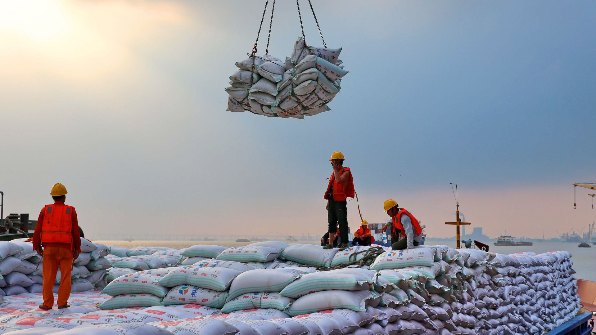 Workers unloading bags of soybeans at a port in China
