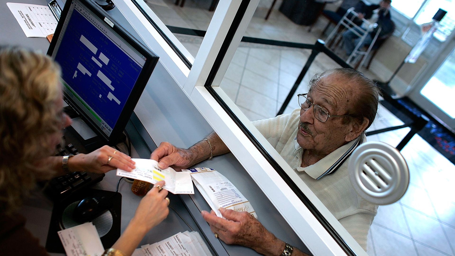 An older man grabs his prescription drugs at a pharmacy counter.
