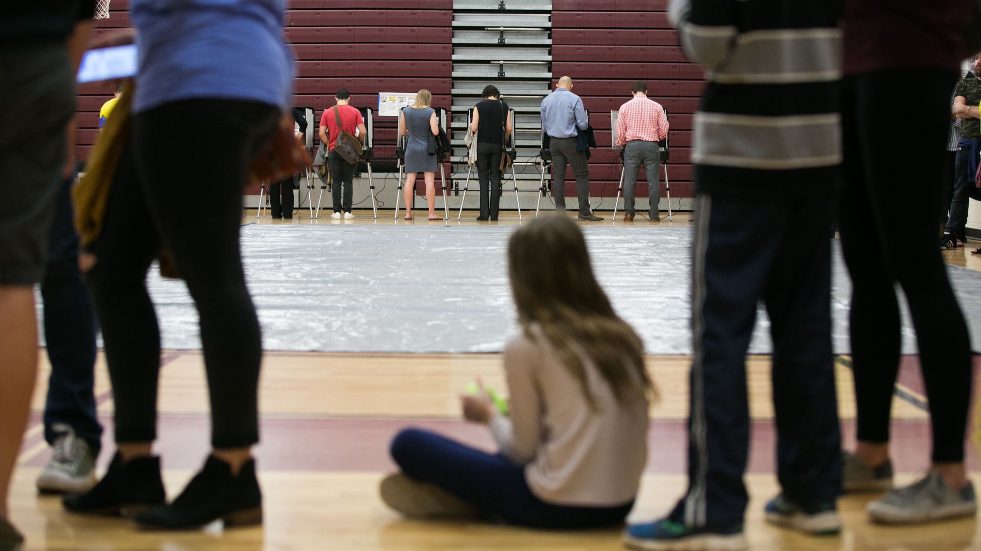 Voters in a gymnasium line up to vote.